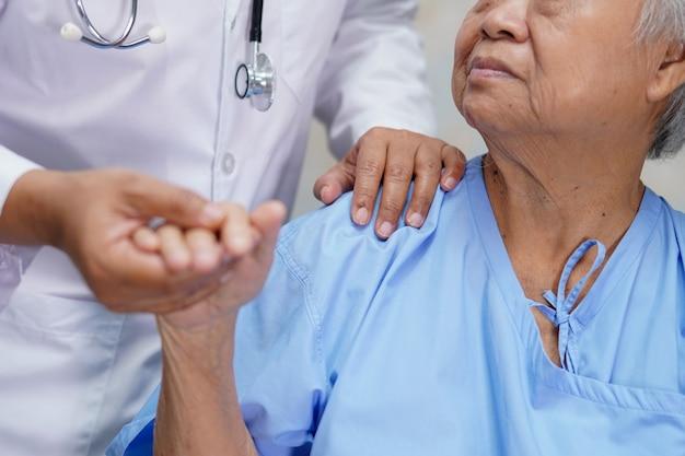 アジアの年配の女性患者に触れるアジアの看護師理学療法士医師