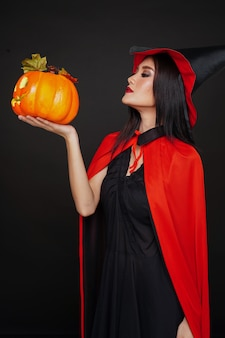 Женщина в шляпе ведьмы и костюм держит тыкву на хэллоуин