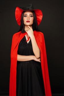 Женщина в шляпе ведьмы и костюм на хэллоуин