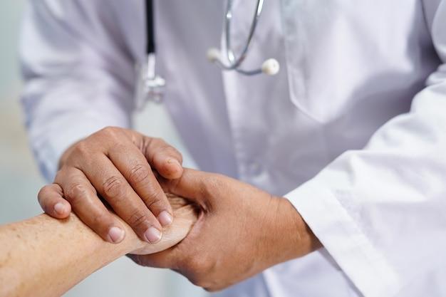 Держа руки азиатский старший пациент женщина с любовью.