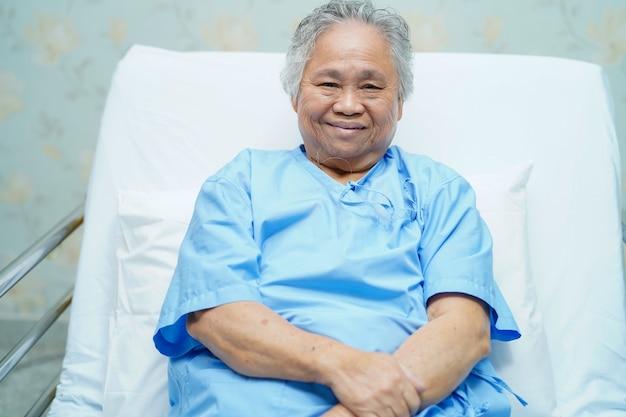 アジアの年配の女性患者は病院のベッドに座って明るい顔を笑顔します。