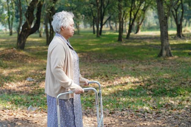 アジアの年配の女性患者は公園でウォーカーと歩きます。