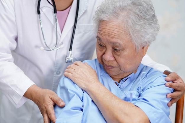 病院でアジアの年配の女性の痛みの肩。