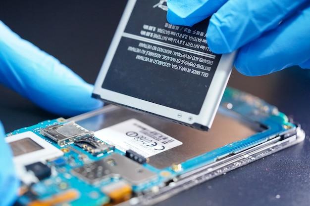 マイクロ回路のメインボードを修理する技術者。
