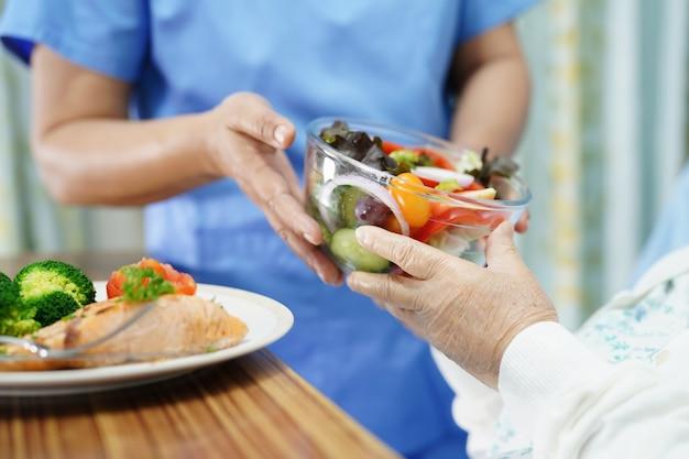 アジアの年配の女性患者が病院で朝食を食べる。