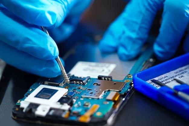 アジアの技術者がスマートフォンのマイクロ回路メインボードを修復します。