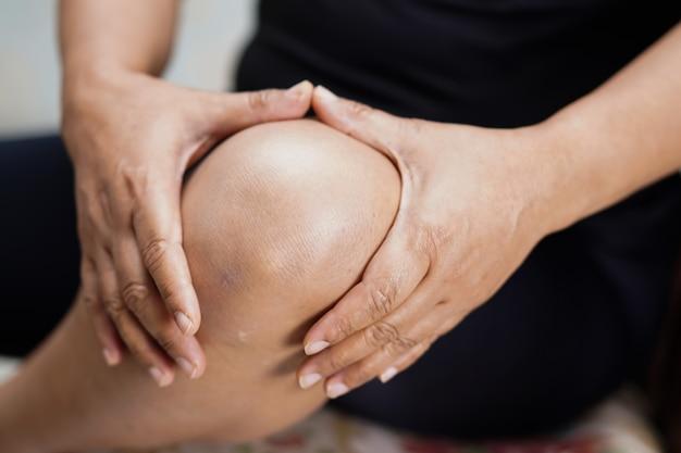 アジアの中年女性の女性患者は、彼女の膝の痛みに触れると感じます。