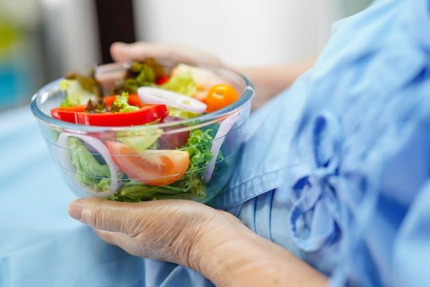 健康的な朝食を食べるアジアの年配の女性患者。