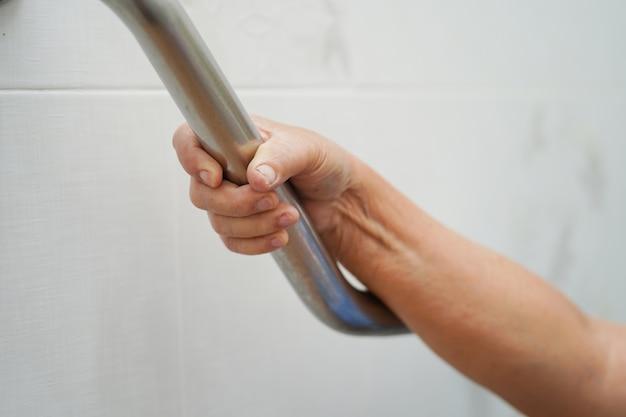 アジアの年配の女性患者は病院でトイレバスルームハンドルセキュリティを使用します。