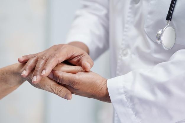 愛をこめてアジアシニア女性患者の手を繋いでいる医者。