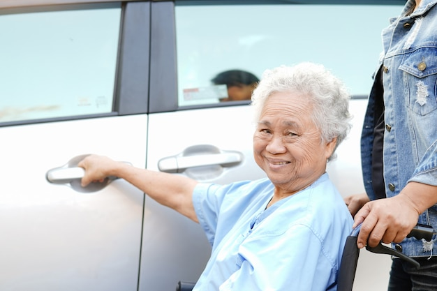 車椅子に座っているアジアの年配の女性患者は彼女の車に着く準備します。