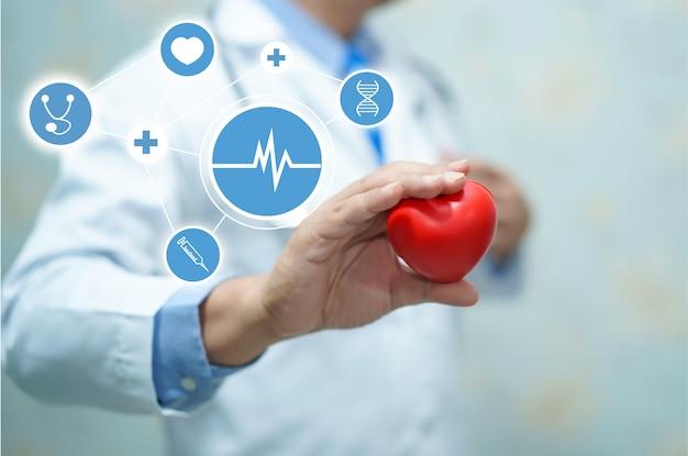 Доктор держит красное сердце в руке в больнице.