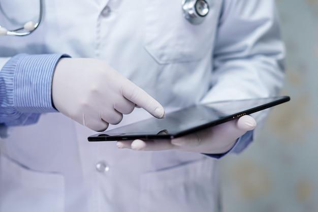 Азиатский умный доктор человека держа цифровую таблетку для того чтобы искать знание разрешает обработку.