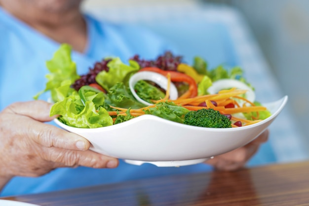 病院で野菜サラダを食べるアジアの年配の女性