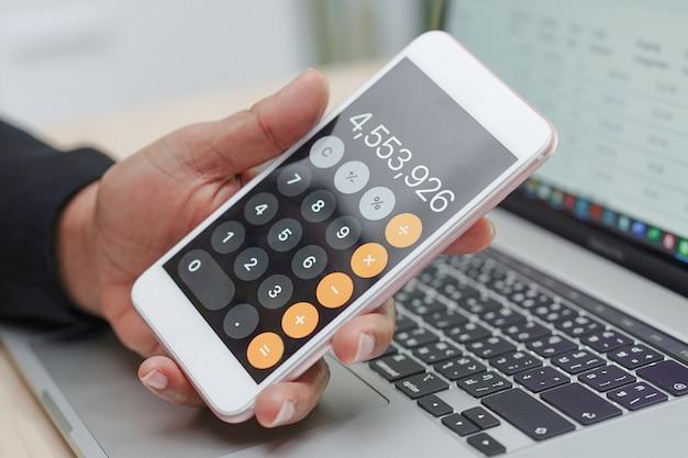 ラップトップを使用してレポートプロジェクトを処理、計算、分析するアジアの会計士