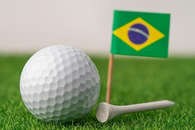ブラジルの国旗と緑の芝生にティーとゴルフボール
