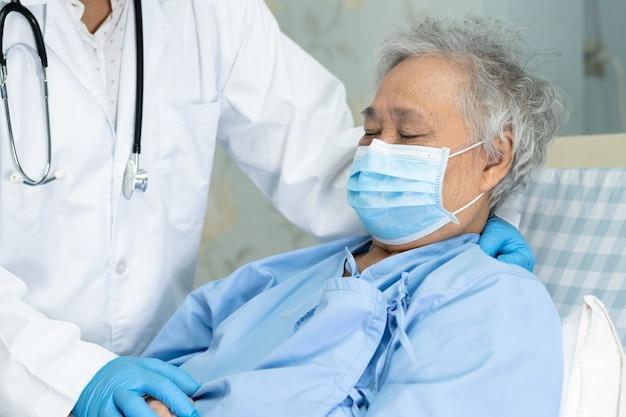 Доктор помогает и заботится азиатская старшая женщина носить маску в больнице