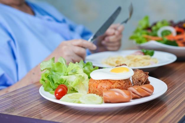 病院で朝食を食べるアジアの年配の女性患者。