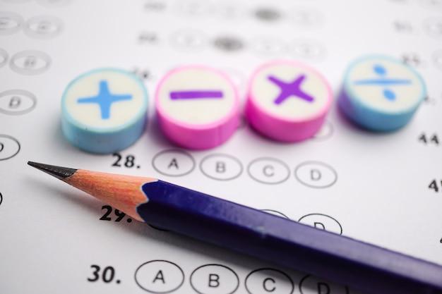 答えのシートの背景に数学記号と鉛筆。