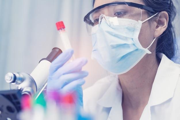 Ученый держит и анализ трубки микро биологического образца с микроскопом в лаборатории для врача в мире.