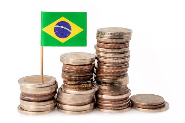 白い背景の上のブラジルの国旗とコインのスタック。