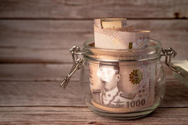 木製の背景の草の瓶にタイバーツ紙幣。