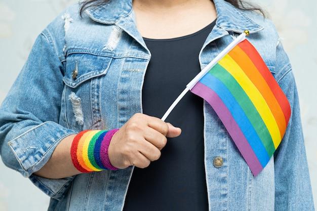Азиатская дама в синей джинсовой куртке или джинсовой рубашке и держит радужный флаг лгбт.