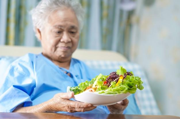 アジアのシニアまたは高齢者の老婦人女性患者が朝食野菜の健康食品を食べる