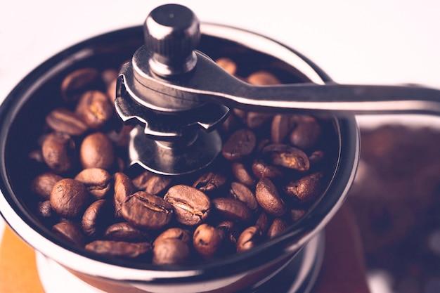 Кофе в зернах жареный в деревянной мясорубке.