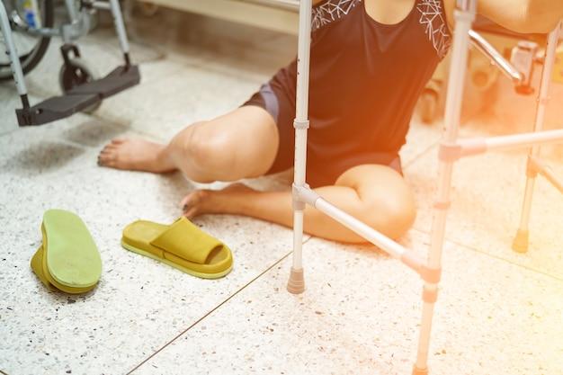 滑りやすい表面のためにリビングルームに落ちるアジアの中年女性の女性患者