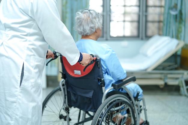 アジアの高齢者または高齢者の女性の患者の患者は、介護病院で車椅子に座っている。