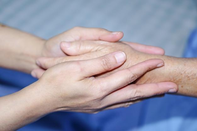 手を触れている手アジアの高齢者または高齢の老婦人の女性。