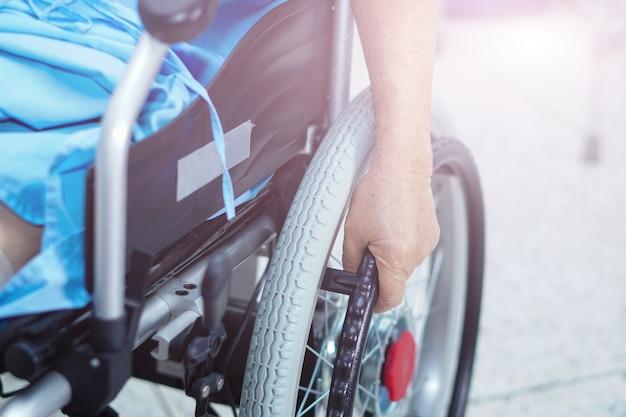 看護病院で電動車いすにアジアの高齢者または高齢の老人女性の患者。