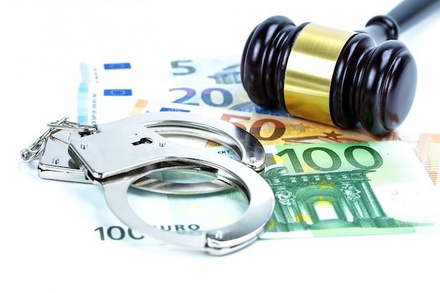 ユーロ紙幣と金属製の手錠。腐敗または詐欺の概念