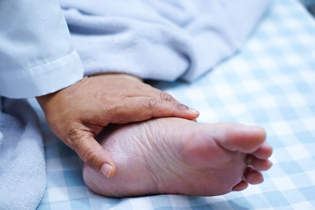 恋人、ケア、励まし、共感しているアジアのシニア女性患者の足に触れている医者。