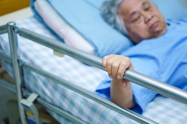 アジアの高齢者や高齢者の老婦人患者が横になって希望を持ってレールベッドを処理します。