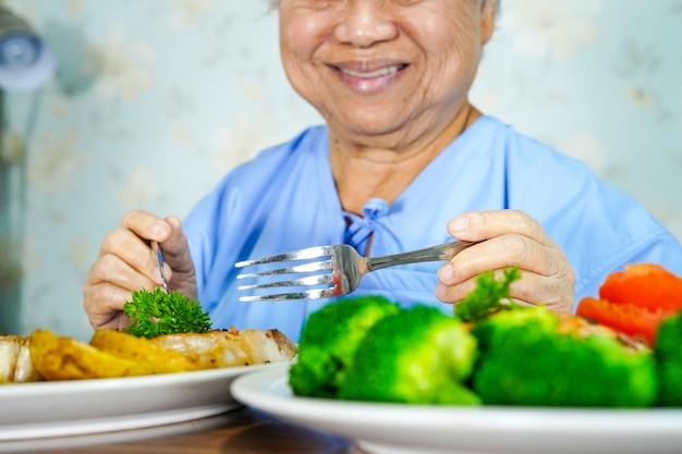 アジアのシニア老婦人女性患者が病院で朝食健康食品を食べる