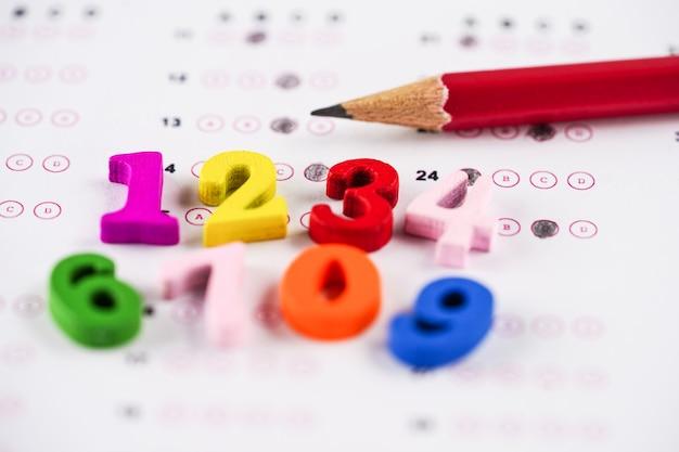 カラフルな数学番号と回答シートの背景に鉛筆