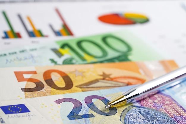 グラフグラフ背景紙の上のユーロ紙幣お金。