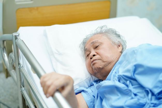 Азиатский пожилой или пожилой пациент старухи ложится ручкой на кровать рельса с надеждой.