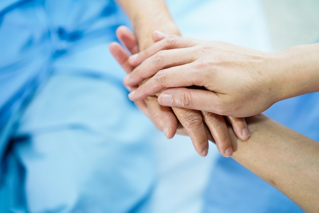 手を握って愛、ケア、励まし、共感を持つアジアの老婦人患者。