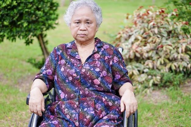 アジアの高齢者や高齢者の老婦人女性は、公園の車椅子で明るい顔の患者を笑顔します。