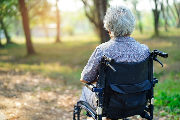 アジアの高齢者や高齢者の老婦人女性患者が公園で車椅子