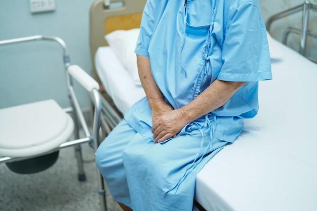 アジアの高齢者または高齢者の老婦人女性患者が看護病棟のベッドの上に座っています。