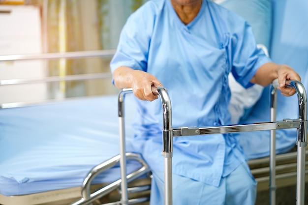 アジアの老婦人の患者がベッドの上に座ってウォーカーと一緒に歩く準備をします。