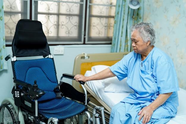 アジアの高齢者または高齢者の老婦人女性患者看護病院病棟で電動車椅子とベッドの上に座って