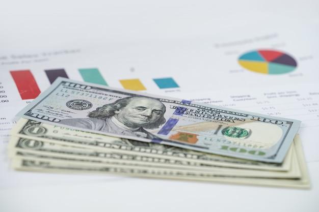 チャートグラフスプレッドシート紙の上の米ドル紙幣お金。