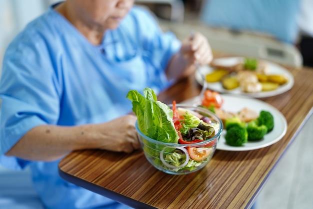アジアの高齢者や高齢者の老婦人女性患者食べる朝食健康食品