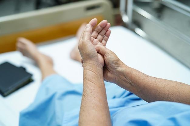 アジアの年配の女性患者は病院で彼女の手を痛みます。