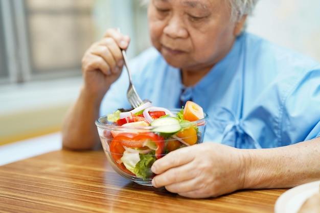 アジアのシニア患者が病院で朝食を食べる